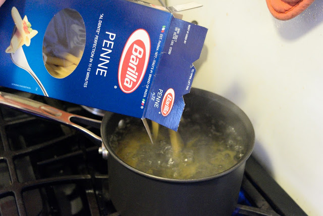 Pasta being added to the salted, boiling, water.