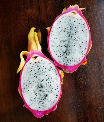 inside of dragon fruit with bright pink exterior, white flesh and black specks for seeds