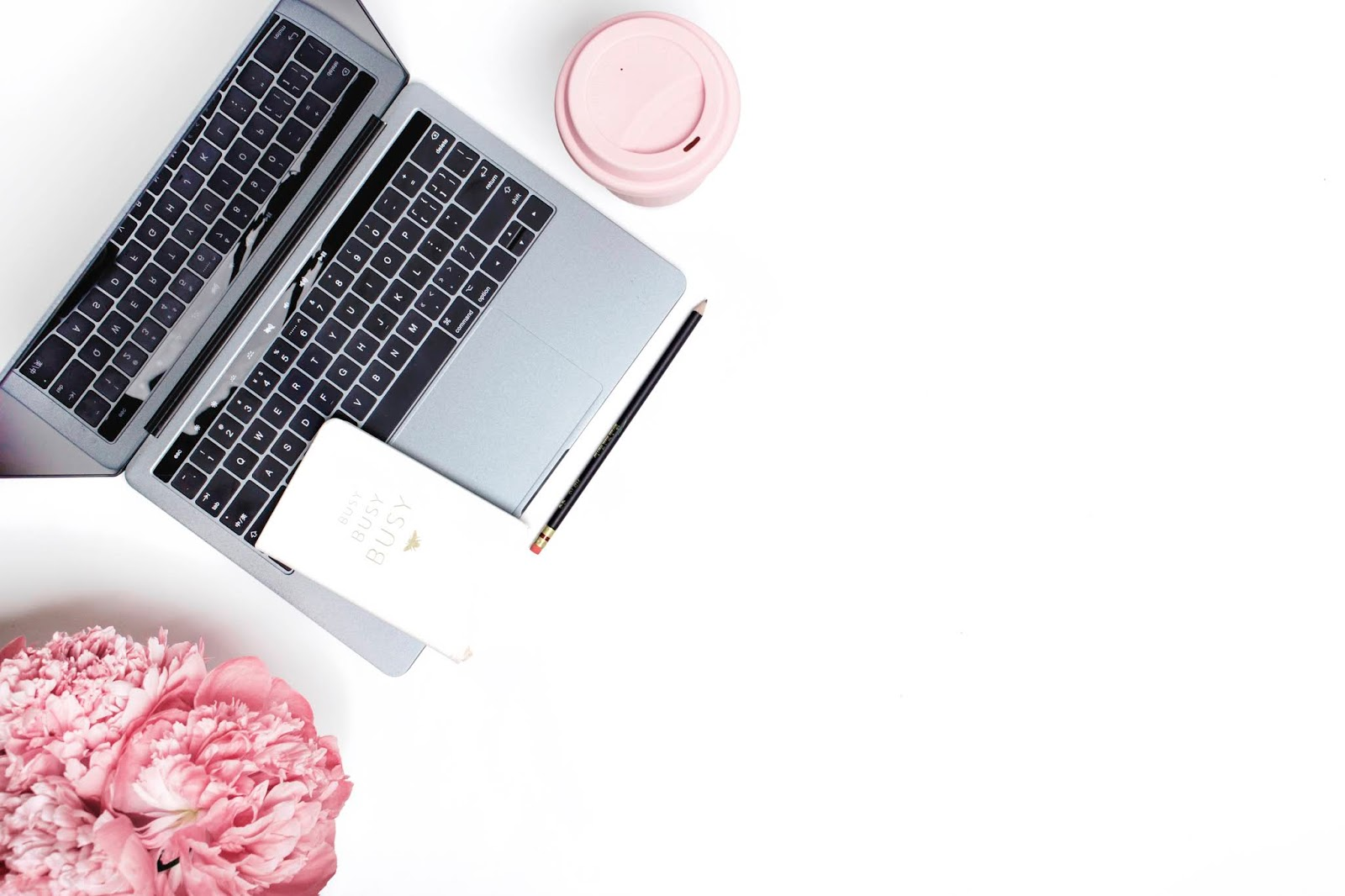 Stock Photo from Ivorymix - Flatlay of a laptop open with a busy planner sitting on it and pink flowers to the left