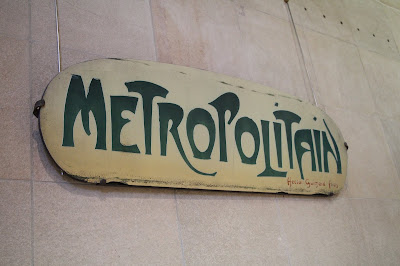 Rectangular cream-colored metal sign with rounded edges saying Metropolitan (as in the Paris subway) in a stylized green font.