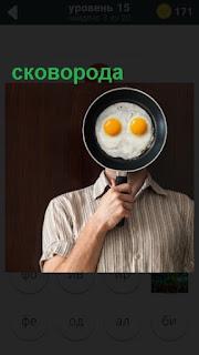 сковорода с яичницей приложена к лицу с желтками внутри как глаза