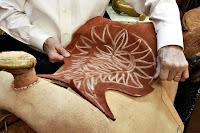 At eyeri yaparken üzerine deri parçası gerdiren bir saraç ustası
