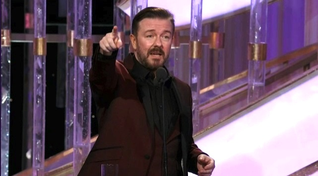 Ricky Gervais on stage, pointing straight ahead of him