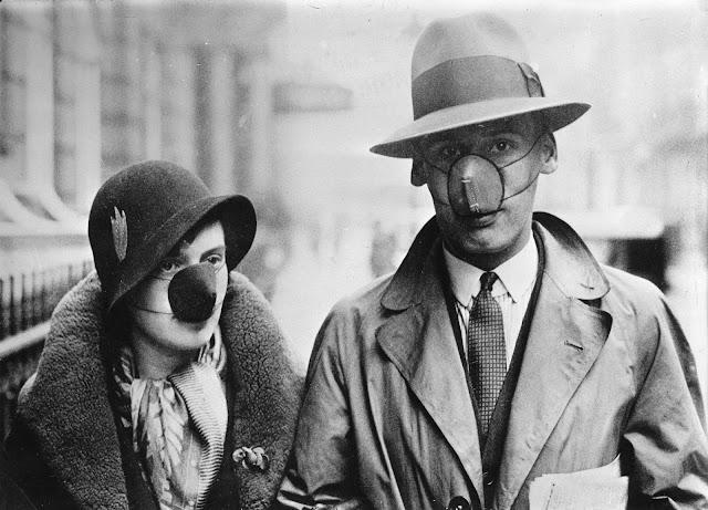 İngiltere'deki insanlar, 1932 dolaylarında İspanyol gribini önlemek için farklı görünümlü maskeler takıyorlar.