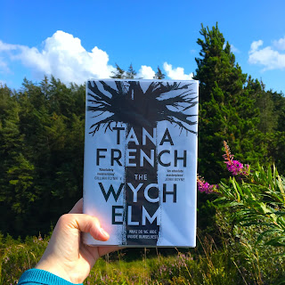The Wych Elm by Tana French being held in front of a Irish hillside scenery with blue skies and white clouds