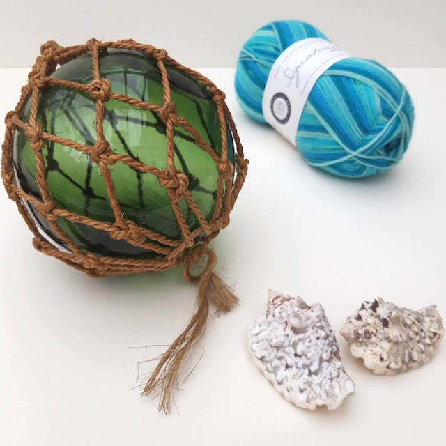 A green glass fishing float, a ball of blue Seascape yarn and two shells on a white background