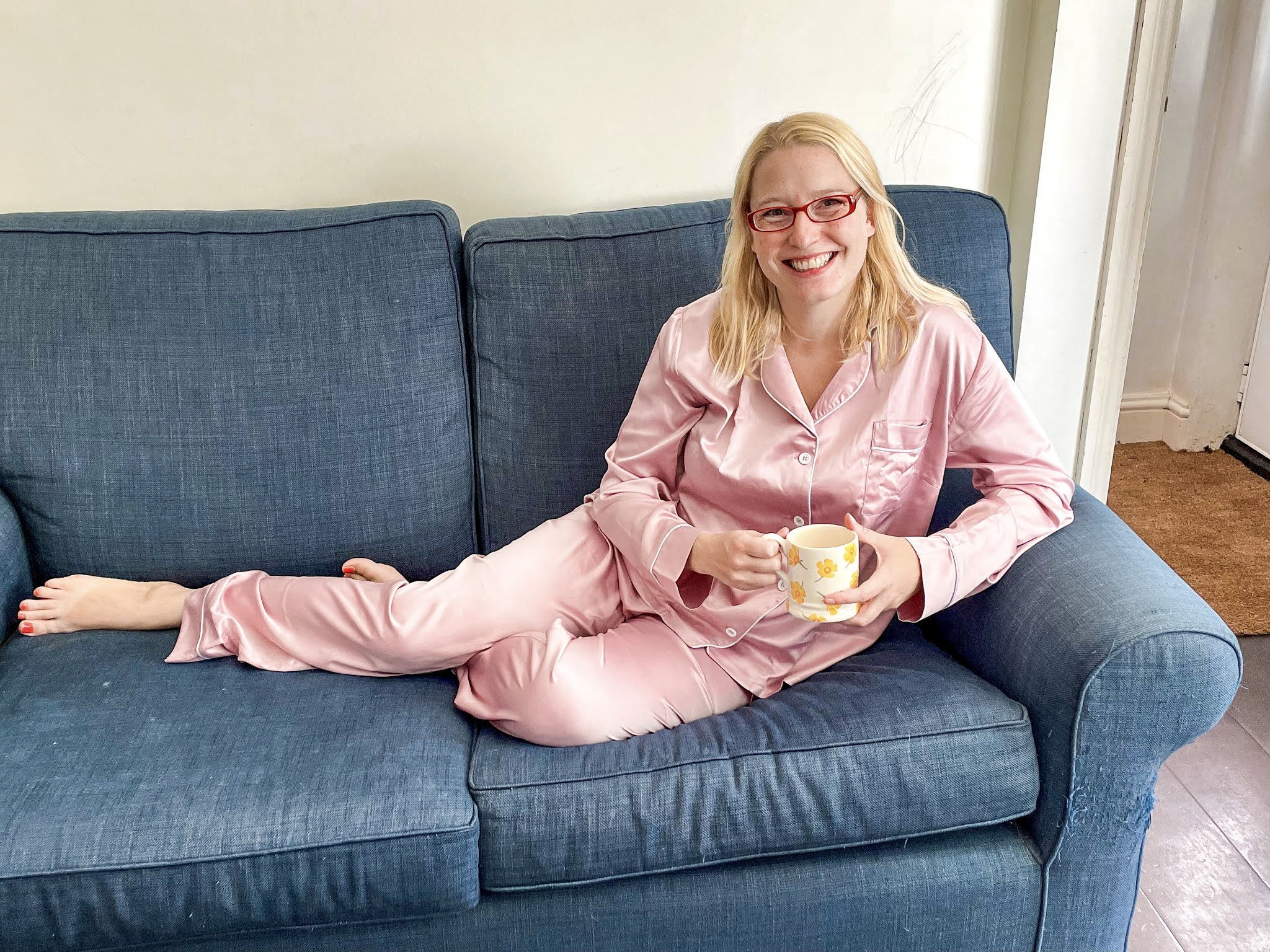 Me on a sofa with a cup of coffee in pink satin pyjamas