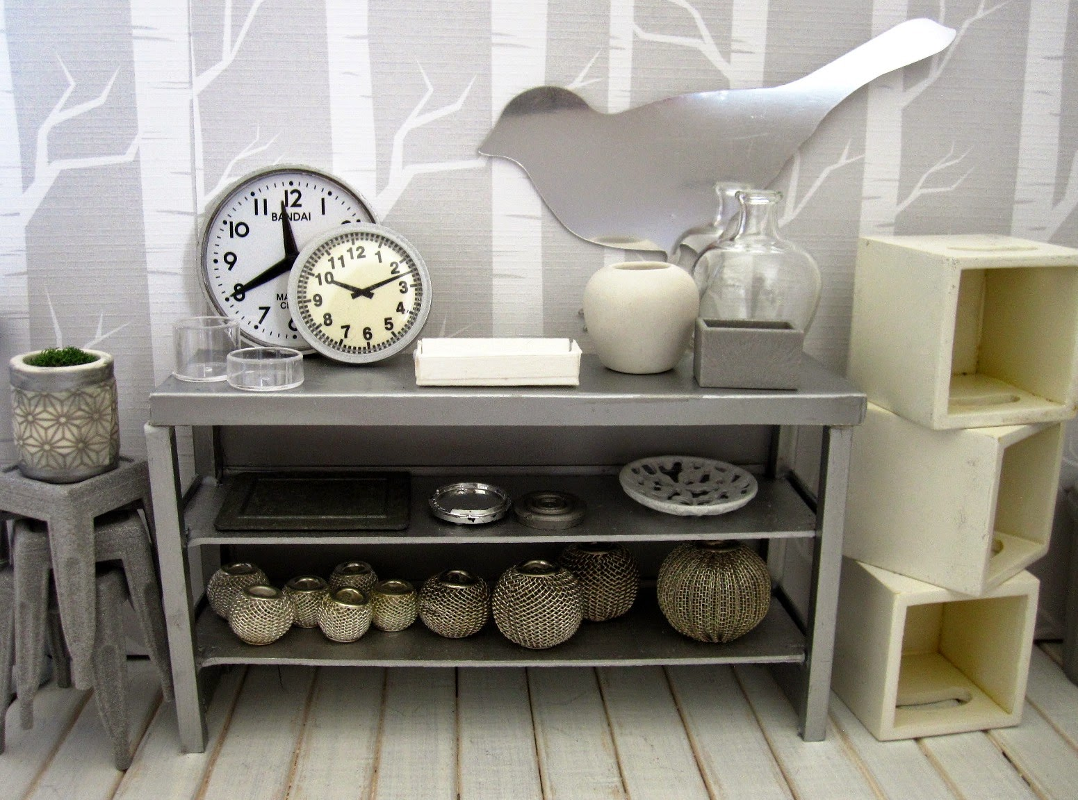 View of a modern dolls' house miniature homeware shop in grey and white. On display is a stack of cafe stools and a grey metal shelving unit with various grey-coloured decor pieces. To the right is a pile of white storage boxes.