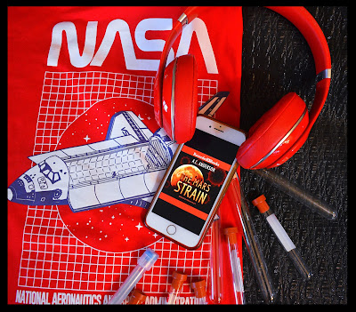 Bookstagram of The Mars Strain audiobook shown on iPhone with red Beats headphones on the top, beneath is a red NASA shirt with a white space shuttle and to the other side is black background and a handful of blood test tubes (empty) with red and blue tops.