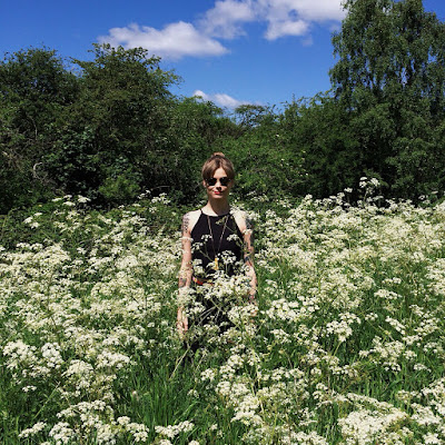 A picture of a tattooed woman in a meadow of Gypsophila flowers