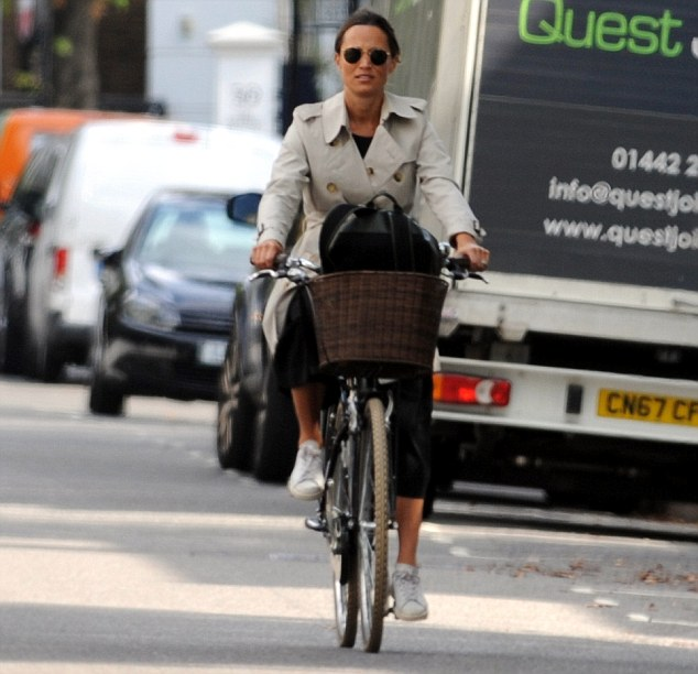 Still on her bike! Pregnant Pippa Middleton looks chic in a black dress and trench coat as she enjoys a cycle in the London sunshine