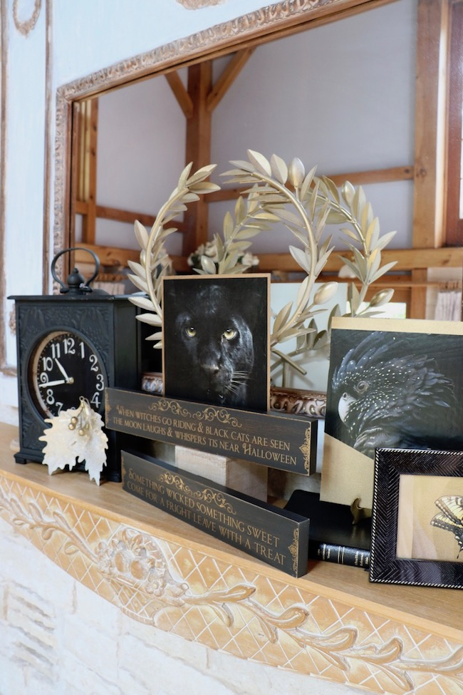 Elegant halloween black and gold mantel uses photos cut from magazines
