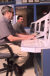 Two men sit at a console desk.