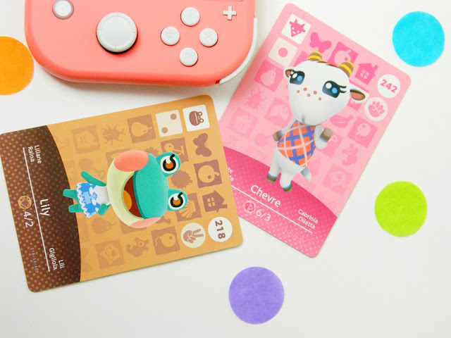 A photograph of a coral-coloured nintendo switch console and two amiibo cards of a goat character and a frog character