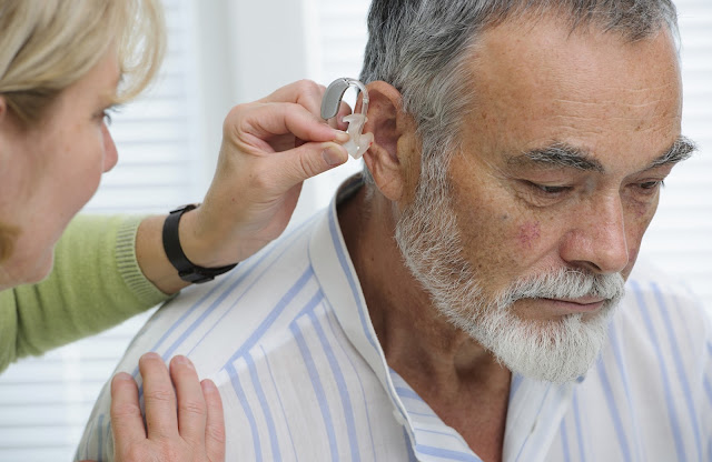 Man being fitted for a hearing aid