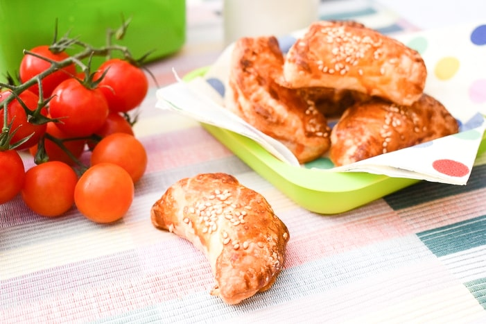 mini spinach and cream chees puff pastry parcels with cherry tomatoes