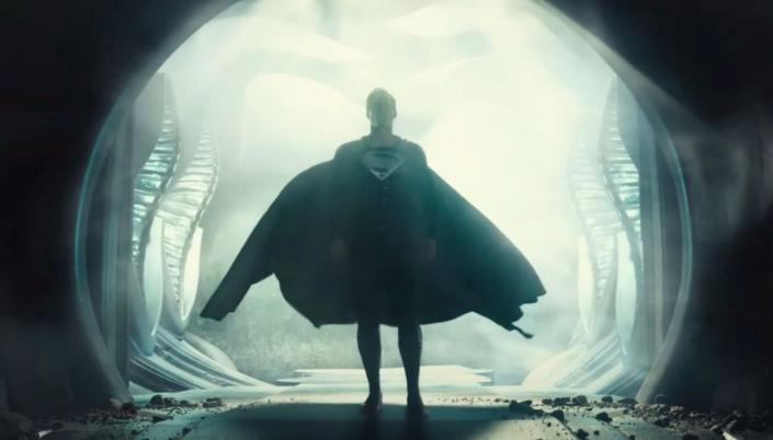 Imagem: a silhueta do Superman em seu uniforme preto com a capa flutuando por trás saindo de um túnel ou escotilha de uma nave alienígena.