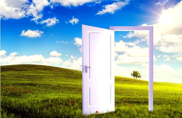 A imagem mostra uma porta branca aberta em um campo se paredes sob um céu azul.