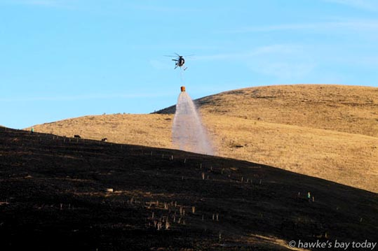 Hastings Fire Service and Hastings District Council Volunteer Rural Fire Brigades, plus choppers, helicopters with monsoon buckets, put out a grass fire on Boundary Rd, Te Hauke, Central Hawke's Bay. photograph