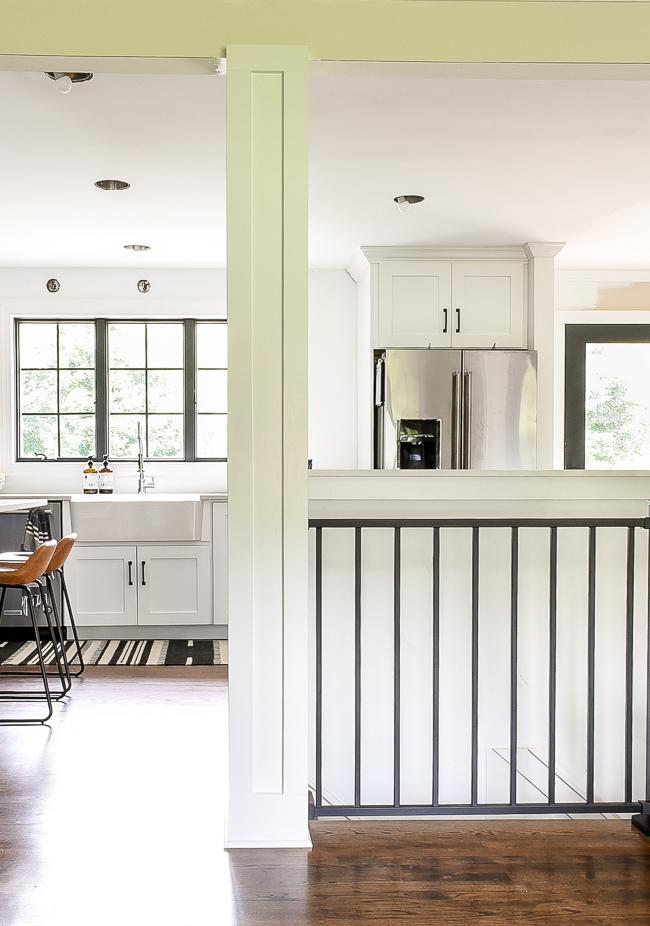 White craftsman style columns and black modern stair railing
