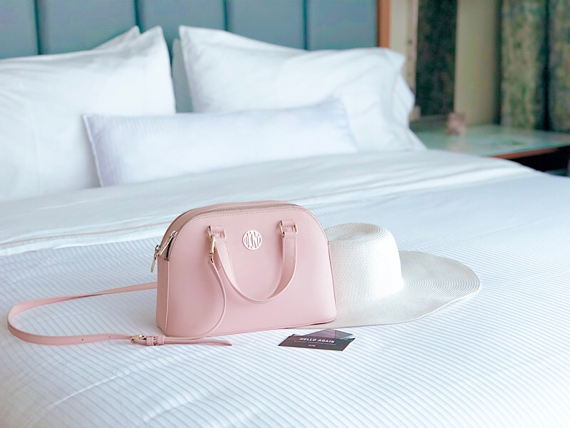 pink DKNY satchel on hotel bed