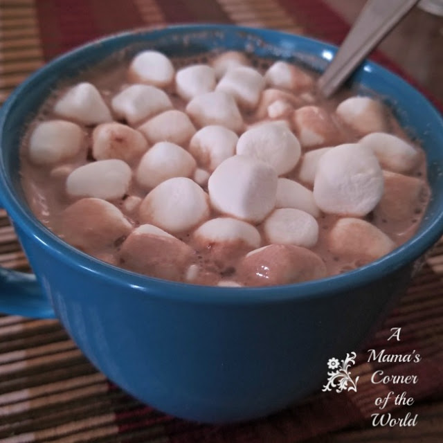 Homemade hot chocolate in a blue mug loaded with mini marshmallows