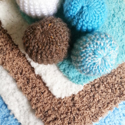 Four one-twelfth scale miniature knitted pouffes on top of four miniature rugs