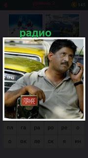мужчина облокотившись о машину слушает радио приложив к уху