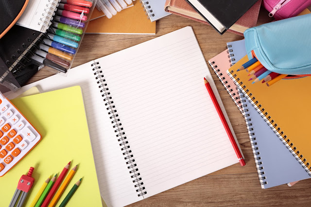 Piles of notebooks, pencils, pens and other school stationary