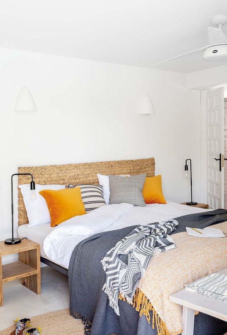 Dormitorio con cabecero de esparto de estilo mediterráneo.