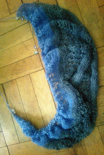 A gradient garter-stitch and lace shawl laid out with live stitches sill on a circular needle.