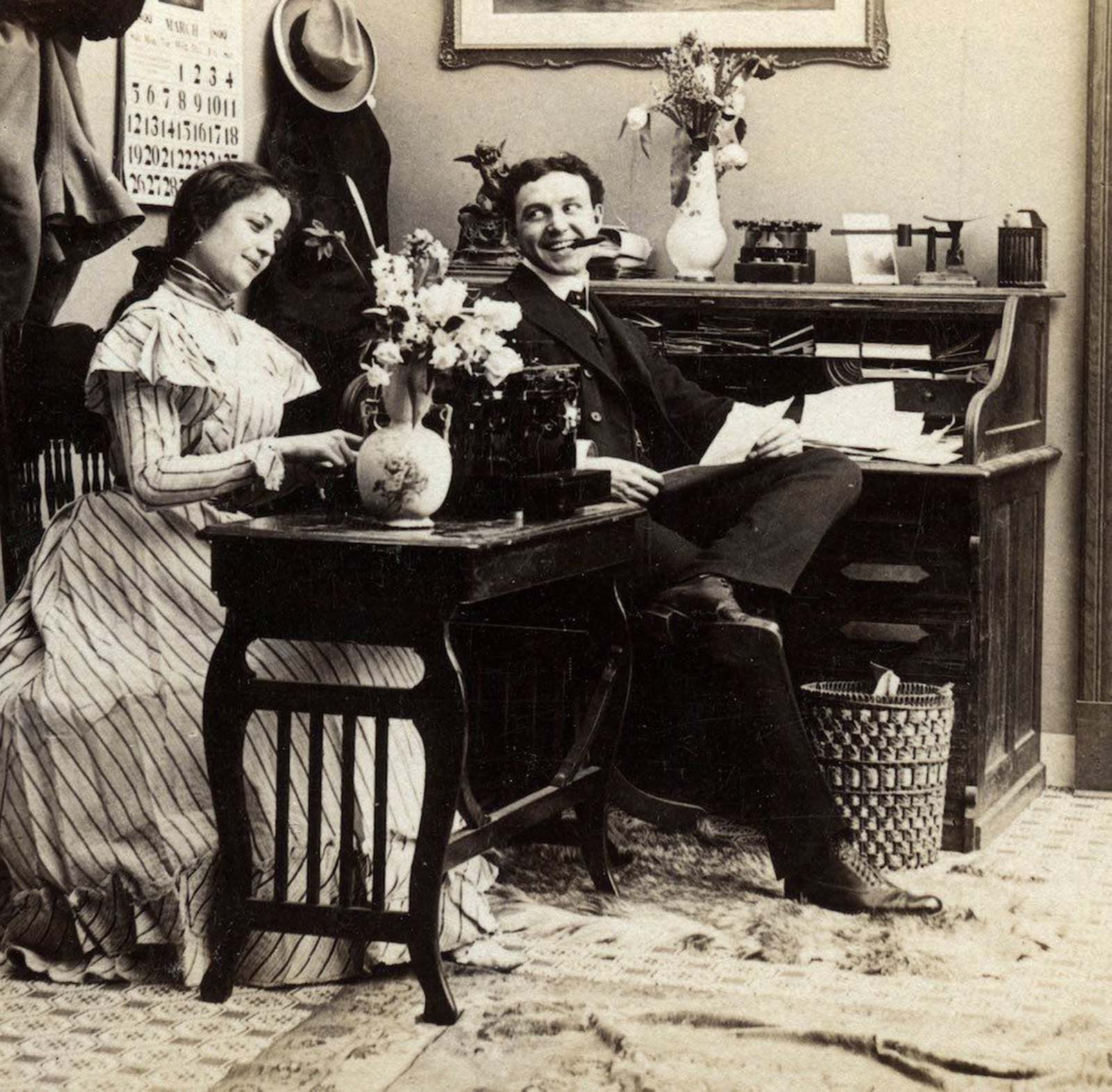 A woman typing in an office. The calendar on the wall of the office dates this image, taken from a stereoscope card originally titled