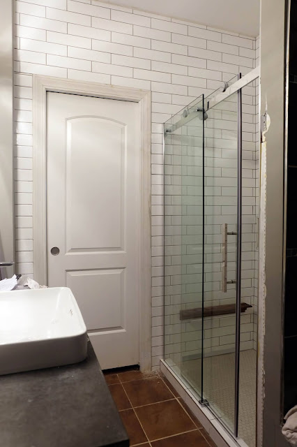 view of shower and tiled wall around door