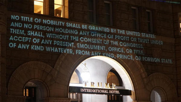 image of Trump hotel with Constitutional section of emoluments clause projected in light on the front of the building