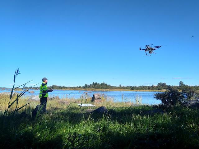 Henkilö lennättää droonia meren rannalla