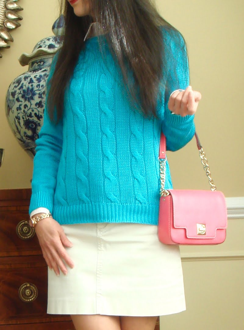 Up close of blue sweater and pink purse.