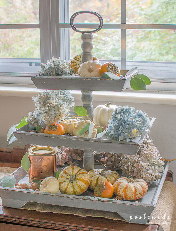 mini pumpkins and dried hydrangeas on a wooden tiered tray