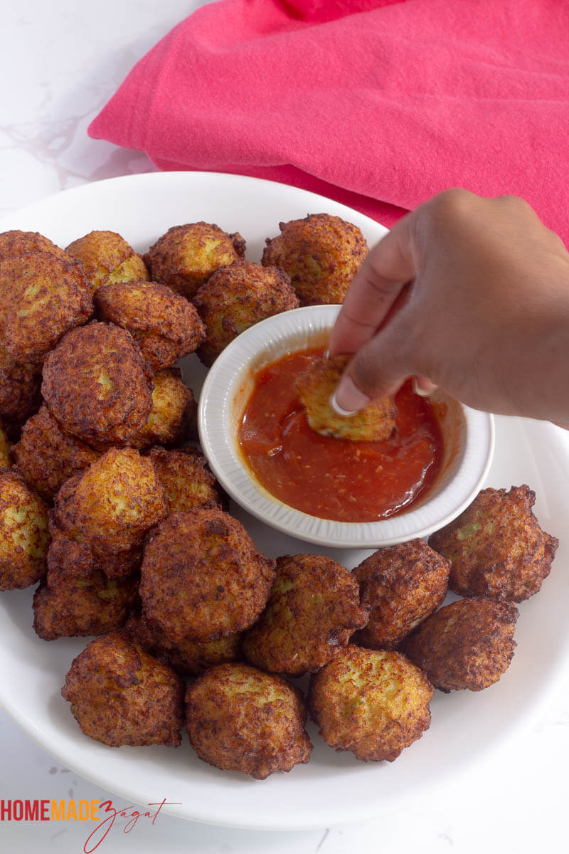 Dipping a fritter into bowl of dipping sauce