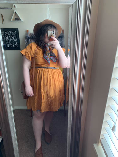 A mirror selfie of an outfit of a brown panama hat, a rust brown paisley neck scarf, yellow short sleeve skater dress and brown d'orsay flats.