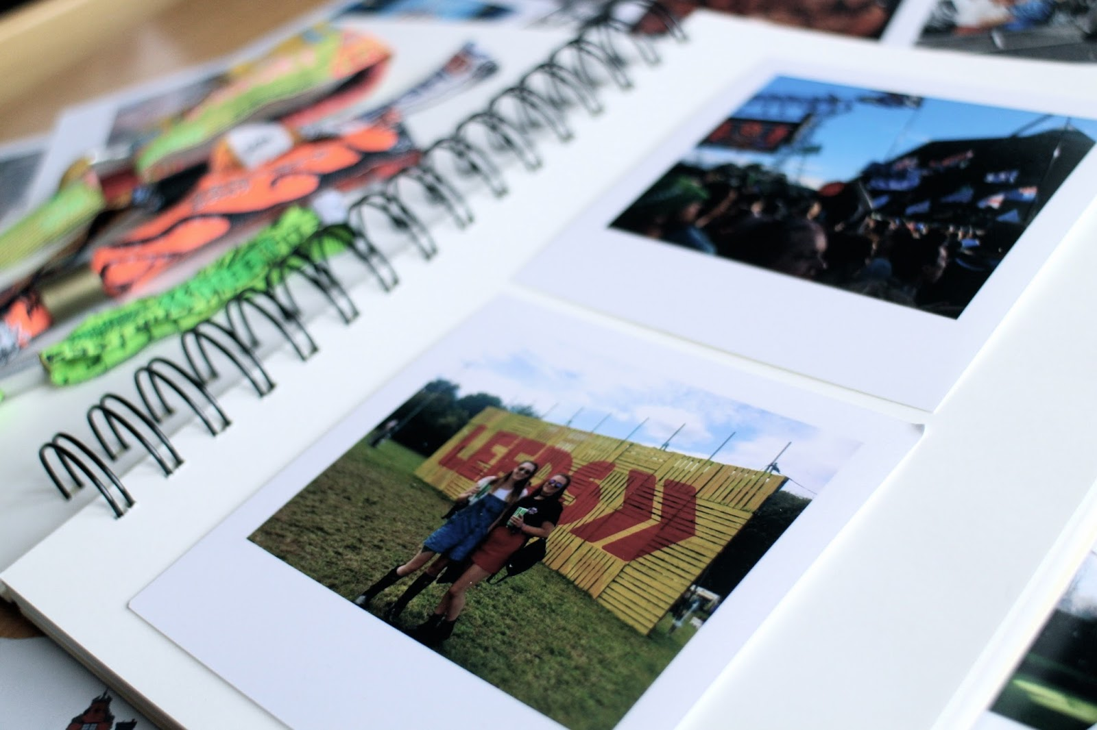 A scrapbook with festival photo prints and wristbands