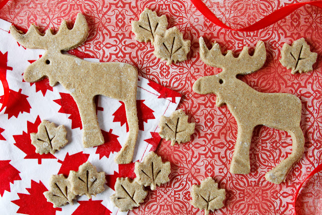 Dog treats shaped like maple leaves and moose on a red background