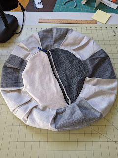Bottom view of not-stuffed dark gray and off-white round meditation cushion showing a zipper going across the center of the bottom circle