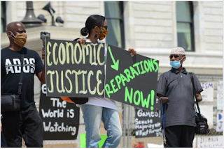 """Men and Women protesting in the Twin Cities area, holding signs reading """"Economic Justice,"""" """"Reparations Now"""" & """"The World is Watching"""""""