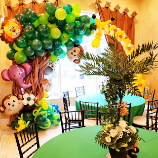 Tropical theme baby shower decoration with balloon arch and flower centerpieces