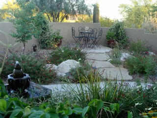 A backyard with a black fountain left front and plants and stepping stones leading to a small table in the rear