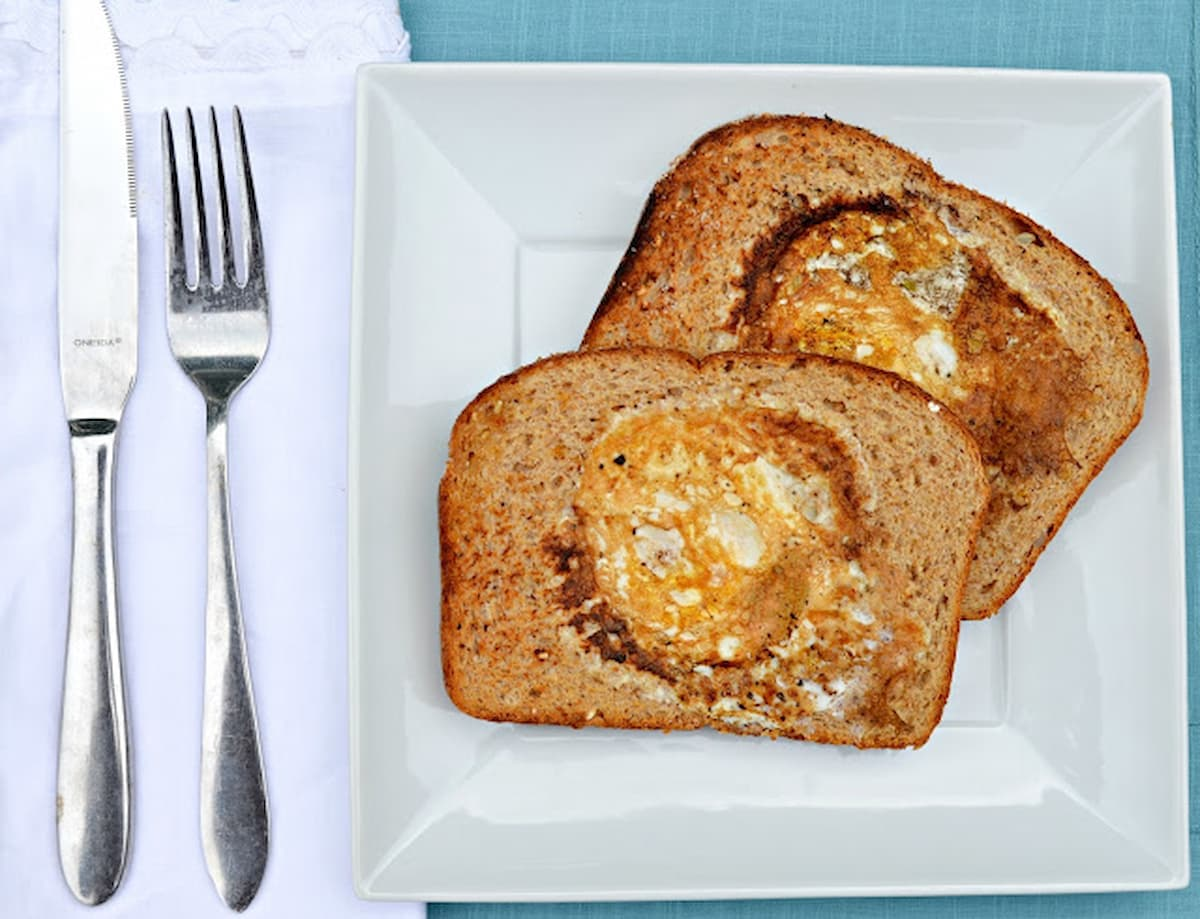 Eggs In A Hole on a white plate. 2 pieces of Bread with a hole cut out and an egg cooked into the center of each piece of bread.