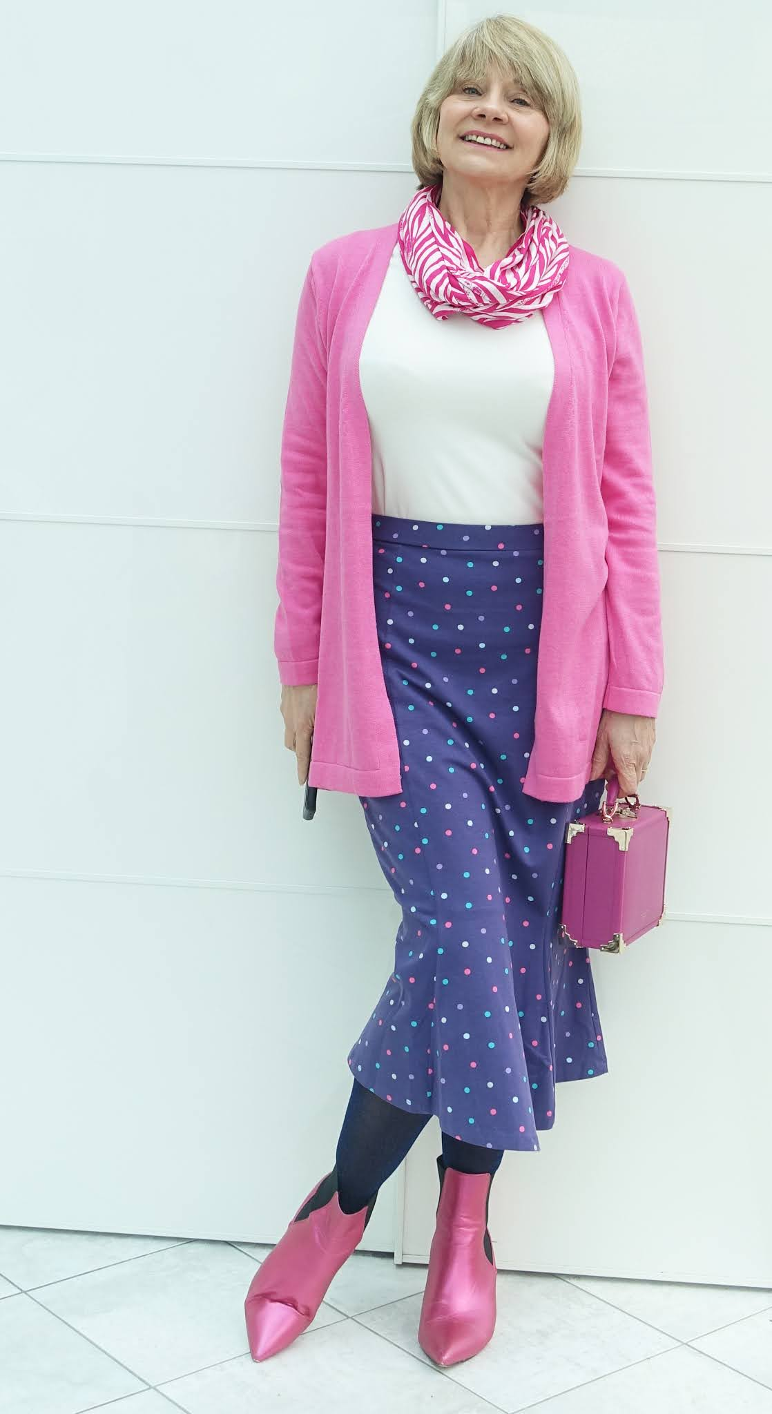 A midi polka dot skirt styled with cerise pink and white by mid life style blogger Gail Hanlon from Is This Mutton