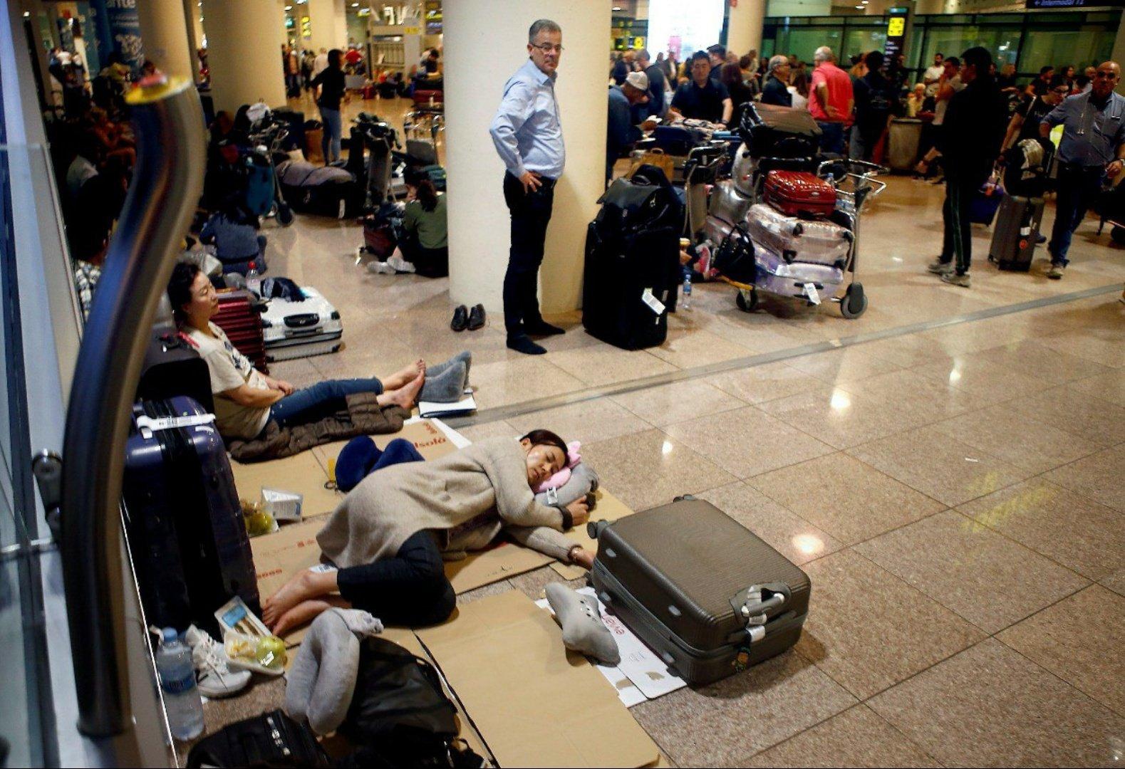 """Lidmašīnu pasažieri guļ uz grīdas """"El Prat"""" lidostā"""