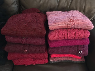 Two stacks of hand-knitted sweaters in different hues of red