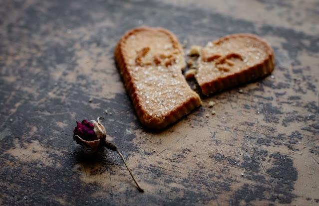A imagem mostra um pão de forma no formato de um coração e partido com uma rosa a seu lado